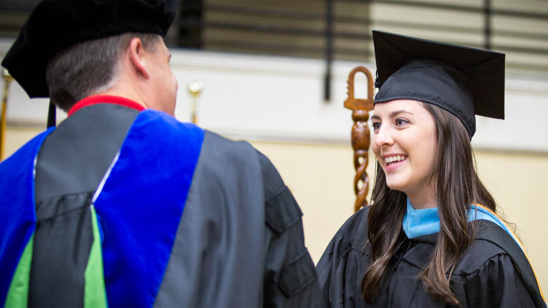 A student receives her master's degree during commencement